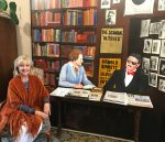 woman sitting next to mural of Sylvia Beach and James Joyce