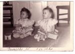 girl twins in satiny dresses sitting by toys, one year old