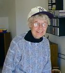 Smiling older woman in glass wearing New York Yankees baseball cap