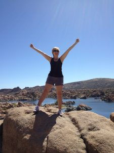 woman standing on rocks arms up victorious