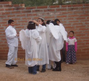 young boys and girls wearing white robes and angel wings over jeans and scuffed sneakers. A girl fixing the crown of another girl