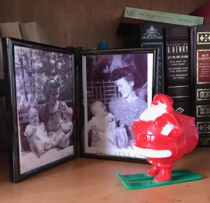 small red plastic Santa next to black and white photos of mother and her young child and twins circa 1947
